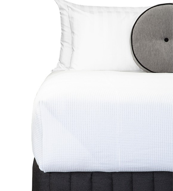 Bed Dressed with Carlo Blanket (White), Suite Valance (Siam Charcoal), Claridge Round Cushion (Genoa Seal Grey), Majestic King & Microball Resort Pillows with Hampton White Stripe Pillowcases